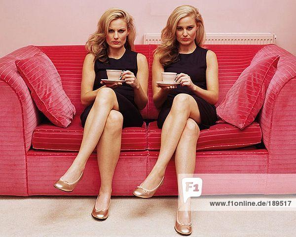Zwei Frauen halten Tassen Tee.