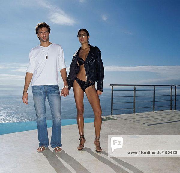 Paar hält sich am Pool an den Händen.