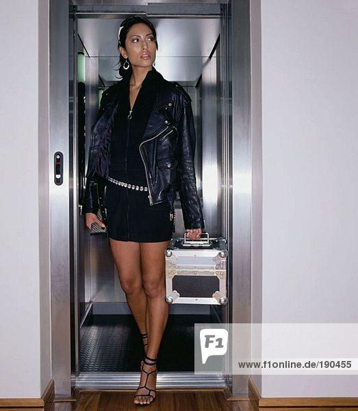 Frau  die aus einem Aufzug steigt.