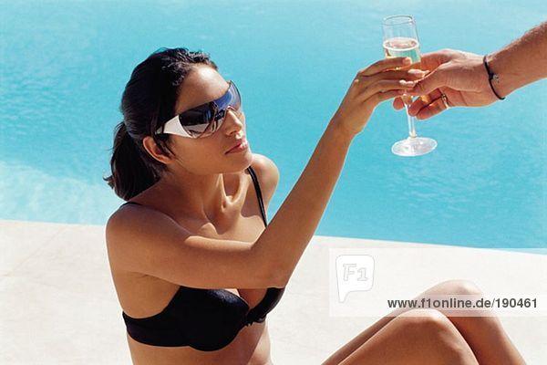 Frau wird an einem Champagnerglas vorbeigeführt