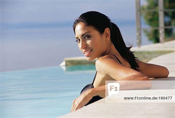 Frau ruht am Rande des Schwimmbades