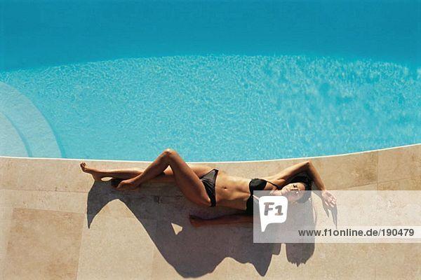Frau beim Sonnenbaden am Schwimmbadrand