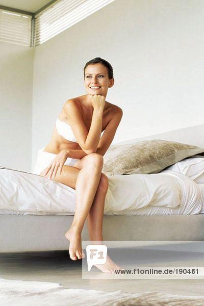 Frau sitzt auf dem Rand ihres Bettes.
