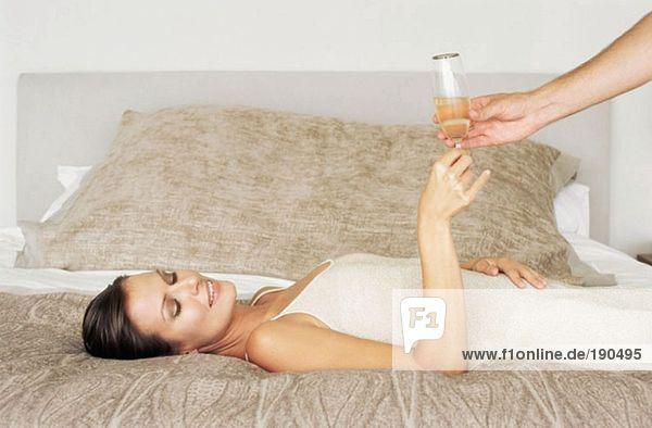 Frau auf dem Bett liegend und mit Champagnerglas