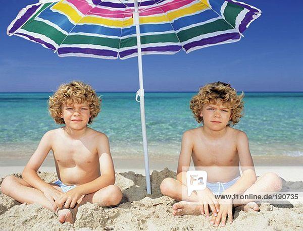Zwillingsjungen unter einem Sonnenschirm