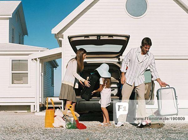 Familie beim Auspacken des Gepäcks aus dem Auto