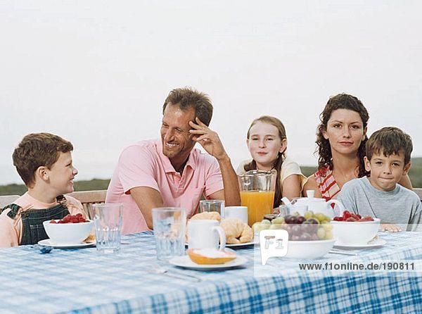 Familie beim Frühstück im Freien