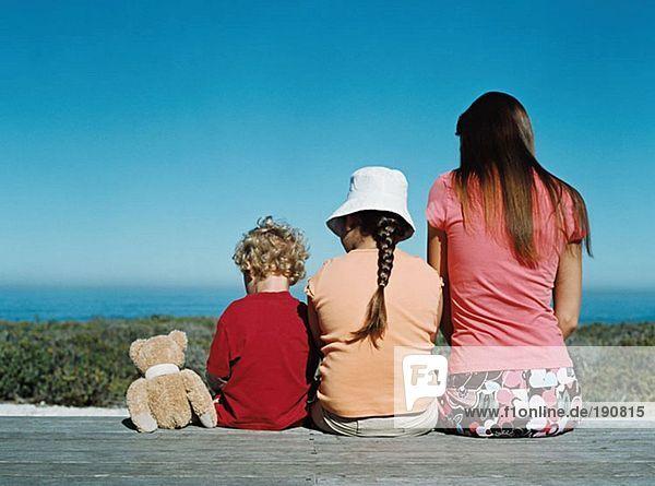 Mutter und Kinder sitzen an Deck