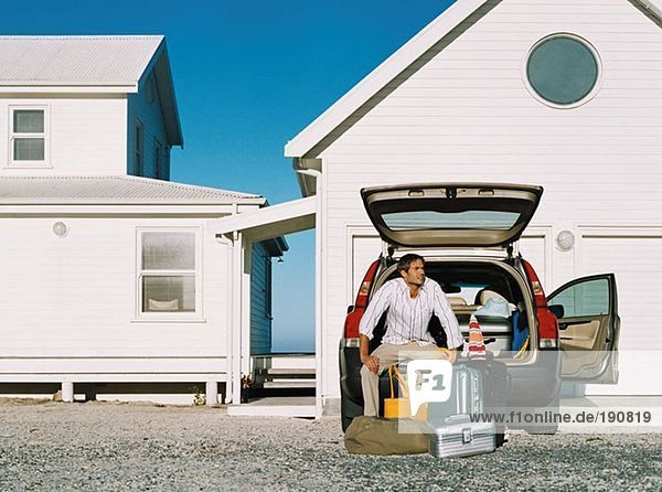 Mann ruht auf seinem Kofferraum