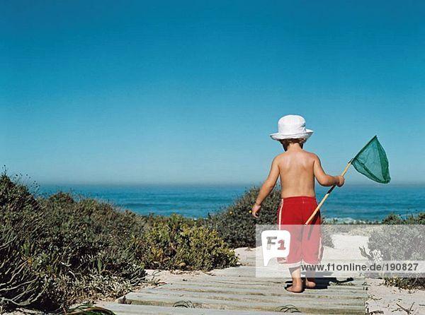 Junge geht mit einem Fischernetz zum Strand