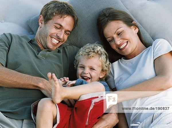 Mutter und Vater kitzelnder Sohn