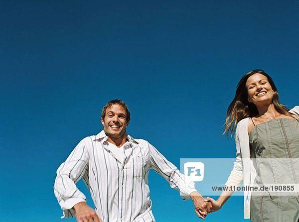 Paar hält sich an den Händen und läuft