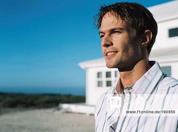 Mann bei Strandhaus