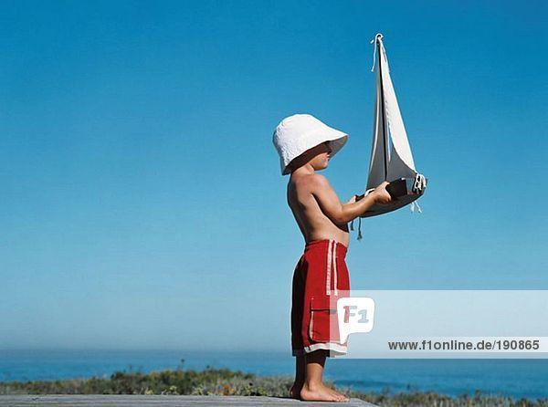Junge mit Spielzeugboot