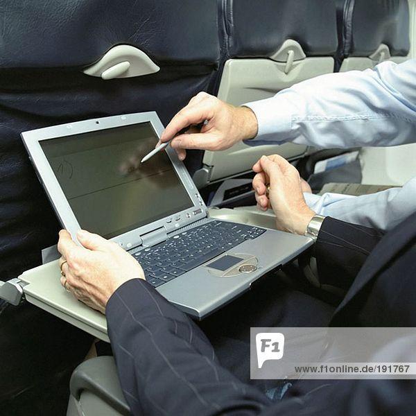 Geschäftsleute mit Laptop im Flugzeug