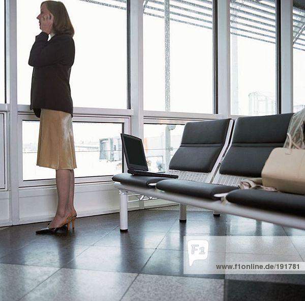 Geschäftsfrau mit Handy in der Abflughalle