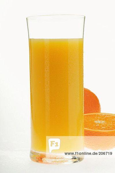 Orangensaft im Glas neben halber Orange