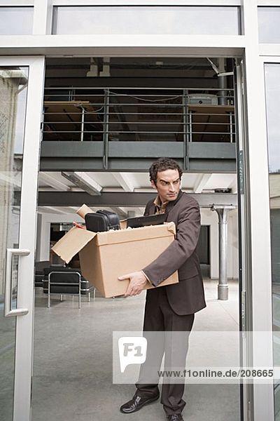 Geschäftsmann mit einer Kiste voller Habseligkeiten