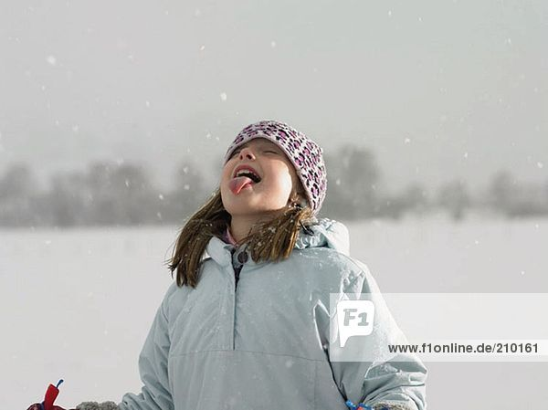 Girl catching snow on her tongue