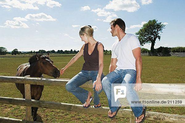 Paar auf einem Zaun sitzend mit Pferd