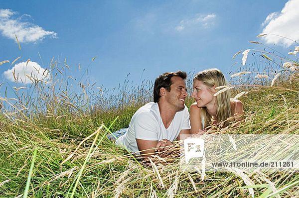 Auf einem Feld liegendes Paar