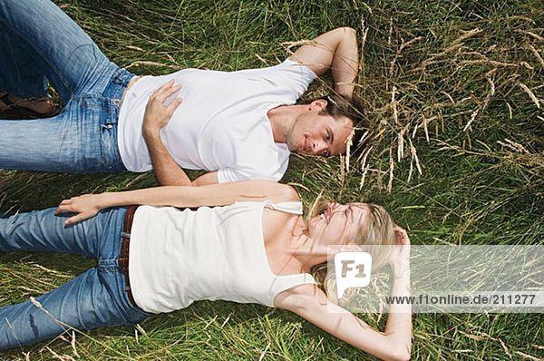 Junges Paar auf einem Feld liegend