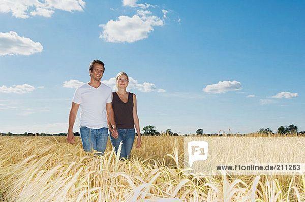 Paar  das in einem Weizenfeld spazieren geht.