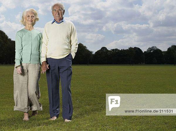 Älteres Ehepaar hält sich im Park an den Händen