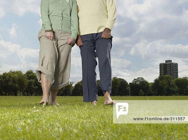 Ältere Paare  die barfuß im Park spazieren gehen