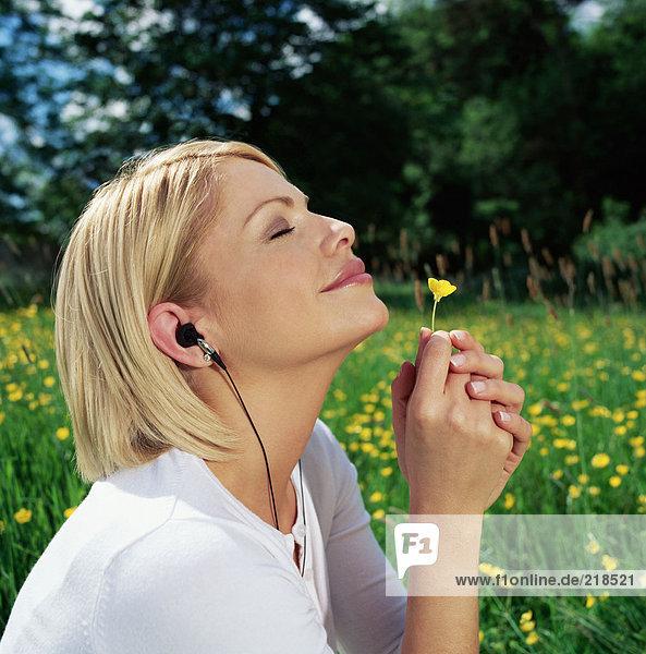 Frau im Kopfhörer riecht Gänseblümchen