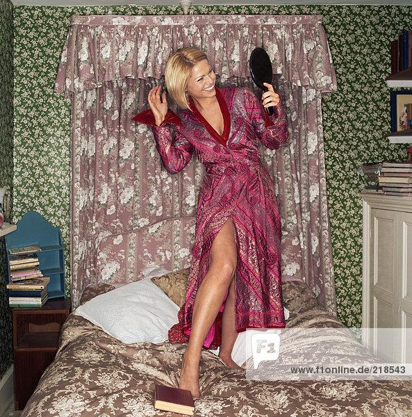 Frau auf dem Bett stehend mit Spiegel