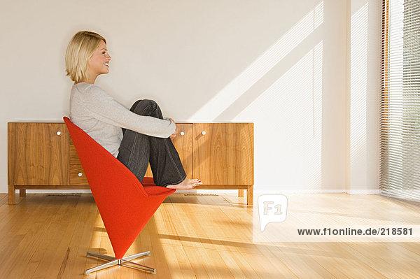 Blonde Frau auf rotem Stuhl sitzend