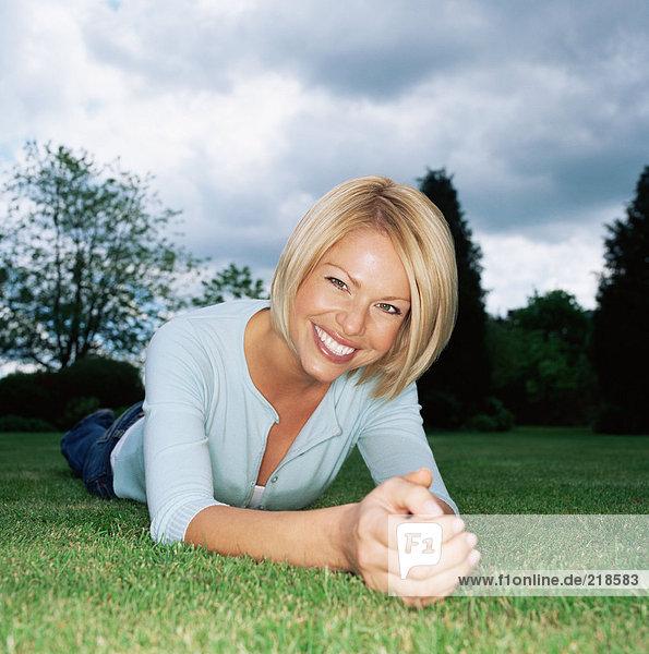 Blonde Frau auf Gras liegend