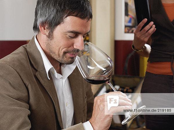 Mann riecht Rotwein