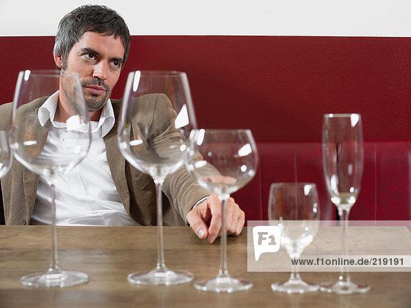Mann am Tisch sitzend mit Weingläsern