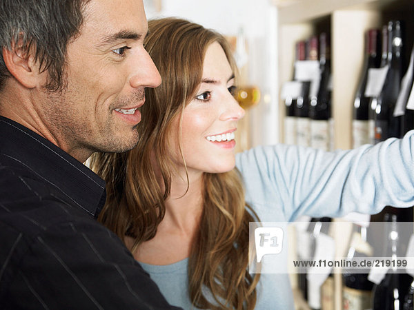 Couple looking at wine bottles