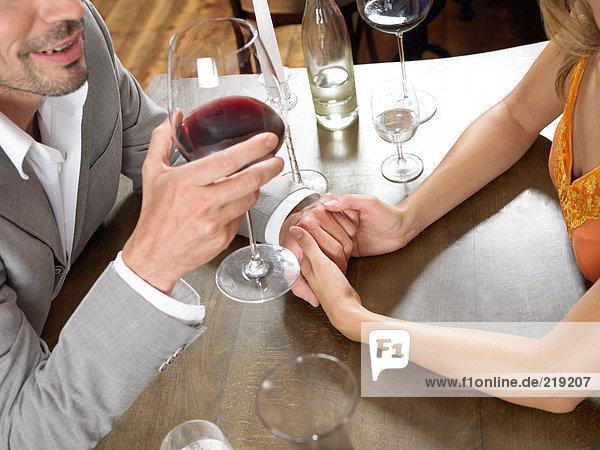 Paar hält Hände am Tisch