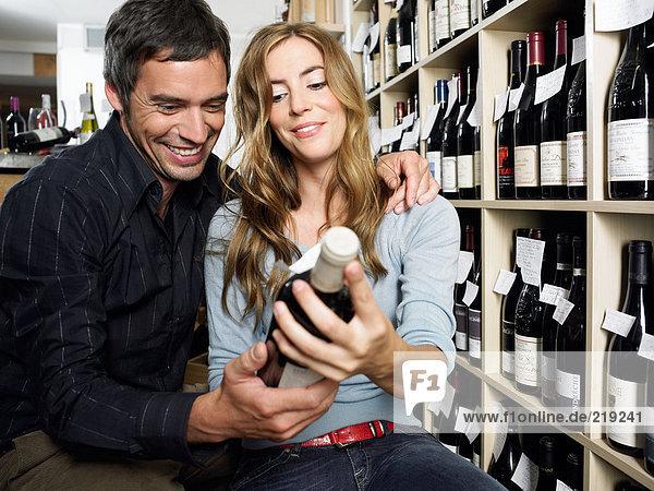 Lächelndes Paar mit Weinflasche