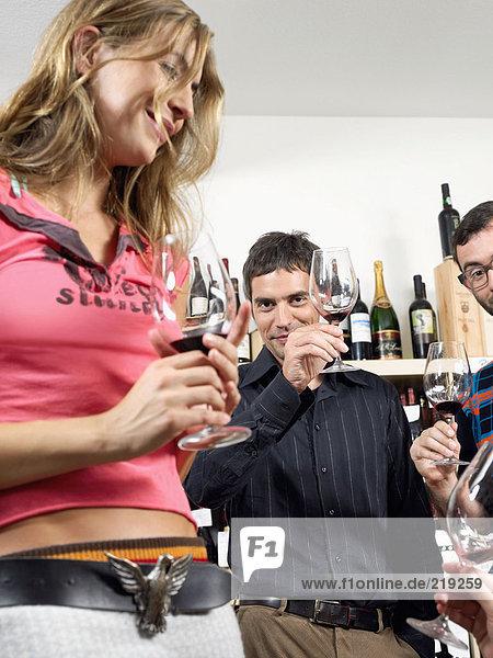Gruppe von Freunden bei der Weinverkostung Toasting