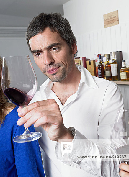 Mann untersucht ein Glas Rotwein