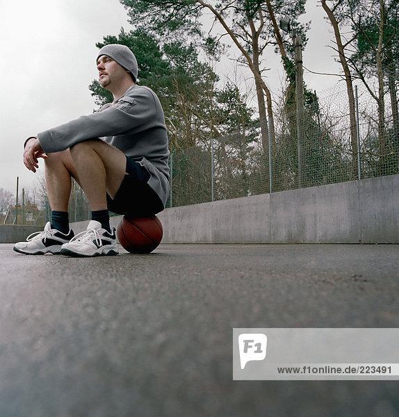 Junger Mann auf einem Basketball sitzend