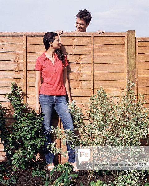 Mann schaut über Zaun auf Frau