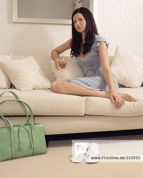 Frau auf dem Sofa mit einem Glas Wein