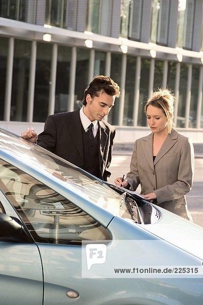 Kaufmann und geschäftsfrau Blick auf Dokument in der Nähe von Auto