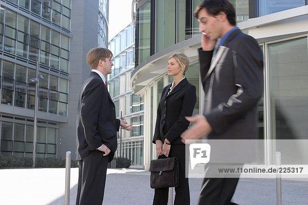 Gespräch auf Handy mit zwei Geschäftsleute sprechen im Hintergrund Kaufmann