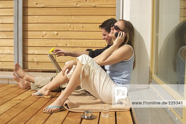 Seitenansicht junge Frau Gespräch auf Handy mit jungen Mann mit Laptop neben ihr