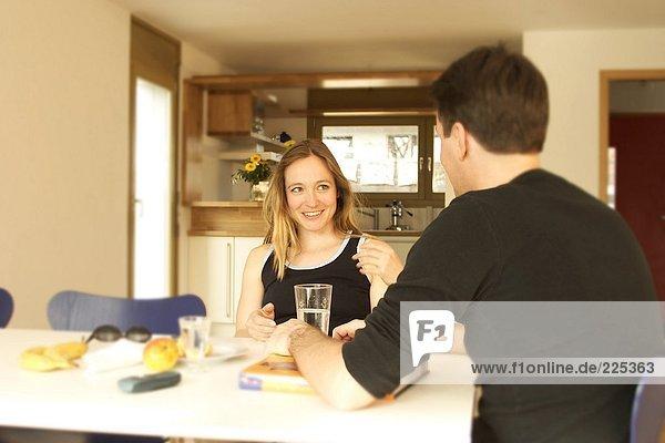 junges Paar sitzen am Tisch und lächelnd