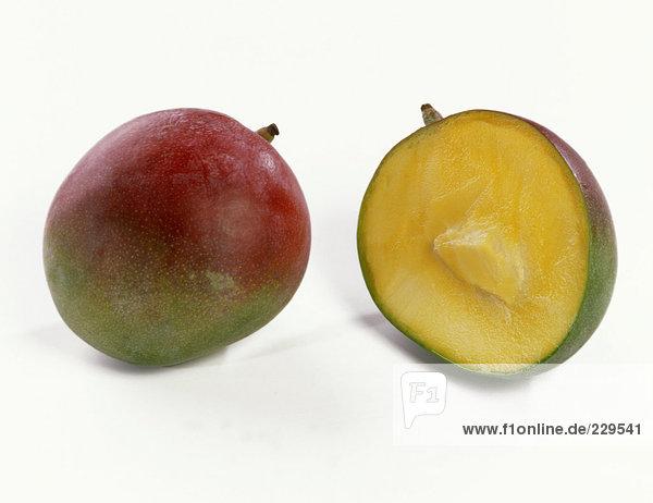 Eine Mango neben einer Mangohälften