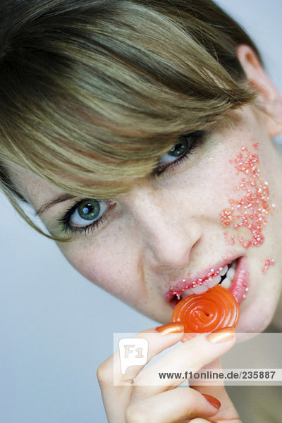Young woman eating fruit jelly  portrait  close-up