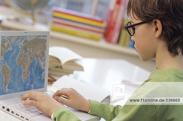 Boy (8-9) using laptop  side view